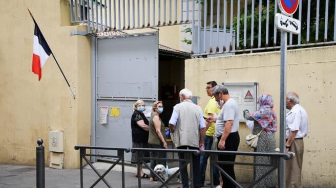 Unos cuantos votantes esperan para depositar su papeleta en las regionales en Francia