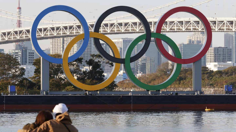Una pareja observa los anillos olímpicos en un puente de Tokio
