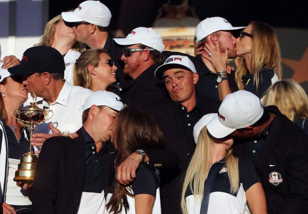 El jugador de golf Rickie Fowler bromea mientras otros golfistas besan a sus mujeres en un torneo en 2016