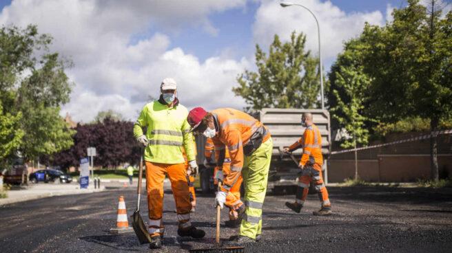 Tres obreros trabajan en una vía en Madrid.