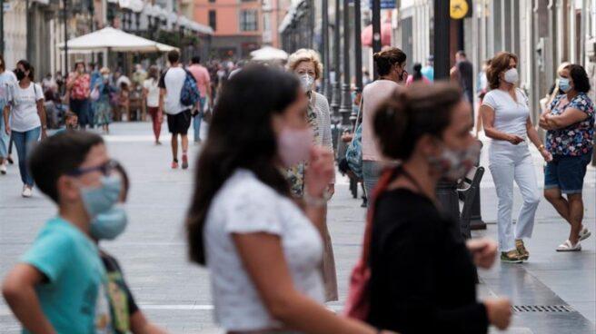 Personas paseando por la calle utilizando la mascarilla
