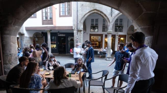 Jóvenes en una mesa de una terraza de un bar.