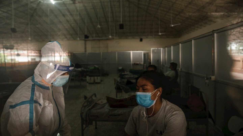 Un sanitario atiende a una paciente en un centro de aislamiento Covid en Katmandú (Nepal).