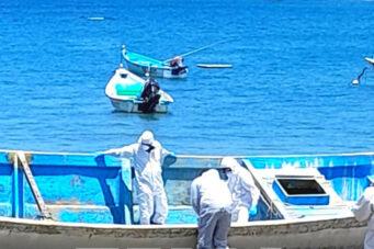 Empleados de la agencia de emergencias de Trinidad y Tobago inspeccionan el cayuco