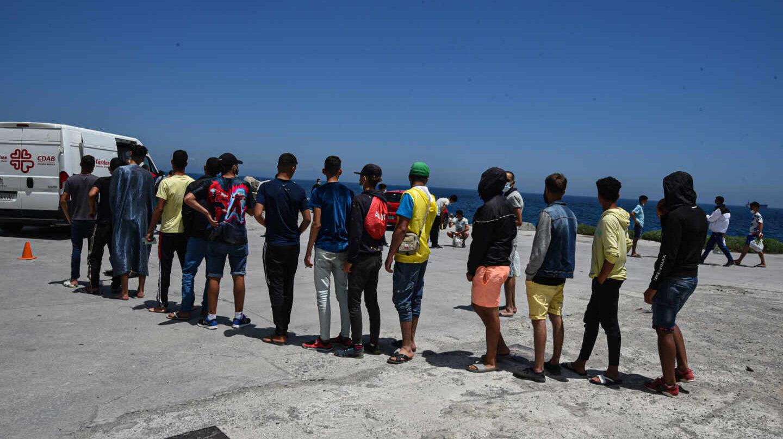 Migrantes hacen cola ante una furgoneta de Cáritas para recoger bolsas de comida en Ceuta.