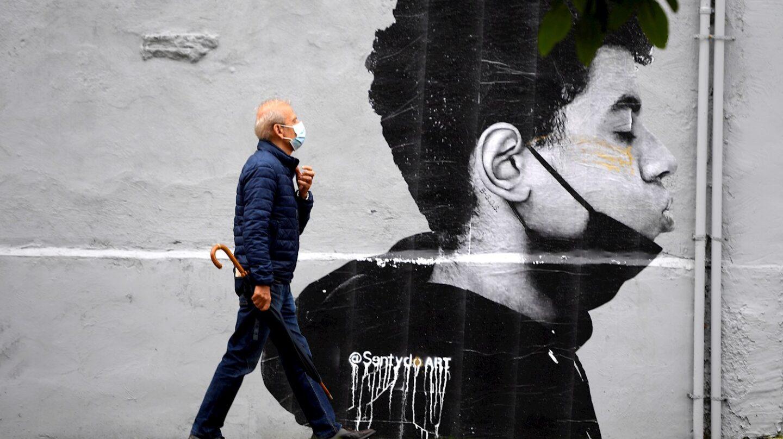 Un hombre camina con mascarilla el primer día sin mascarilla obligatoria en exteriores. Lo hace delante de una obra del artista @Sentydo ART en una campaña dedicada a los besos sin mascarillas.