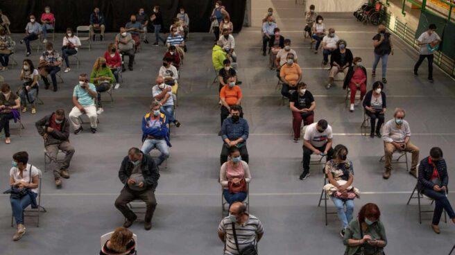 Varias personas esperan tras recibir la vacuna en el pabellón de deportes Paco Paz, en Orense.