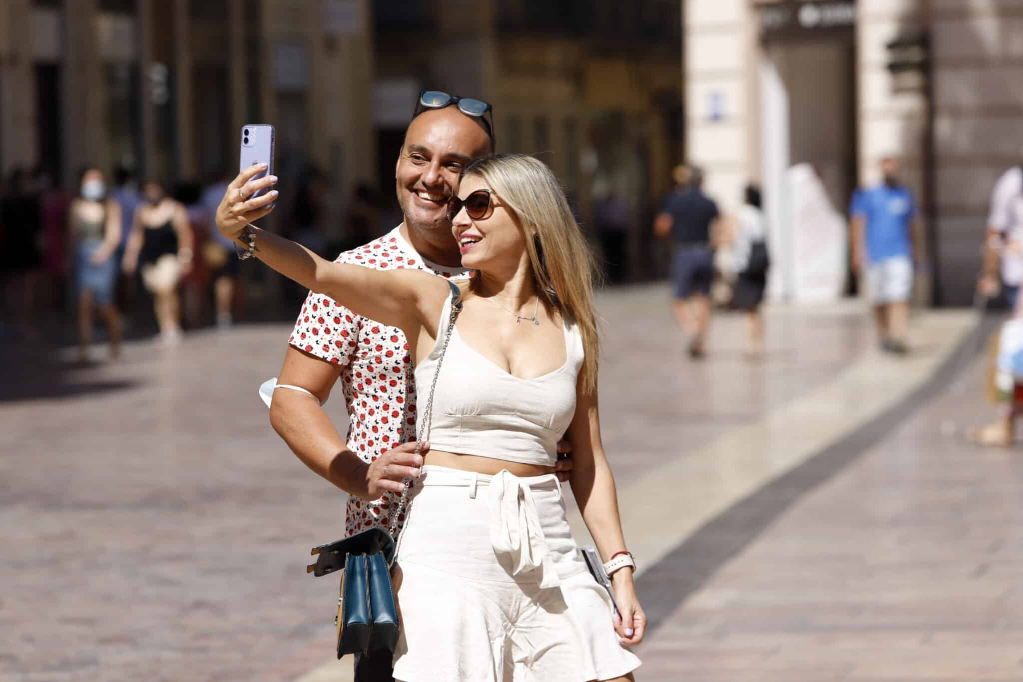 Dos jóvenes se hacen una foto sin mascarilla en la calle Larios