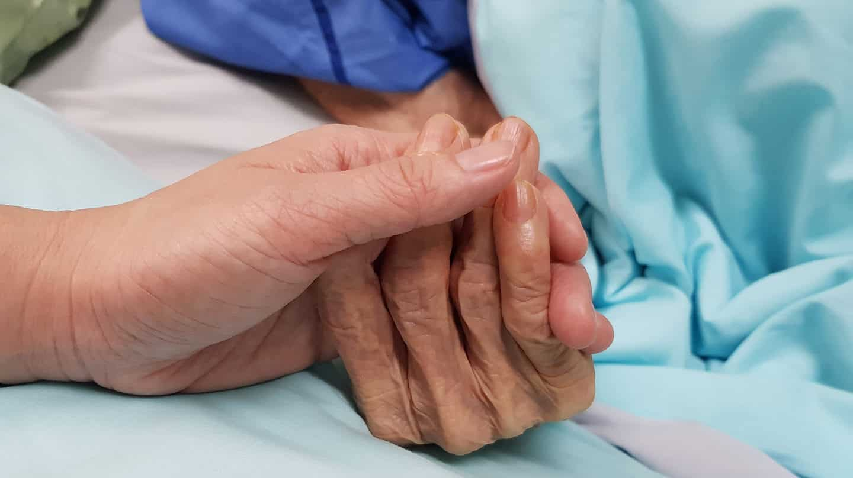 Imagen de un primer plano de dos manos entrelazadas en una cama de hospital
