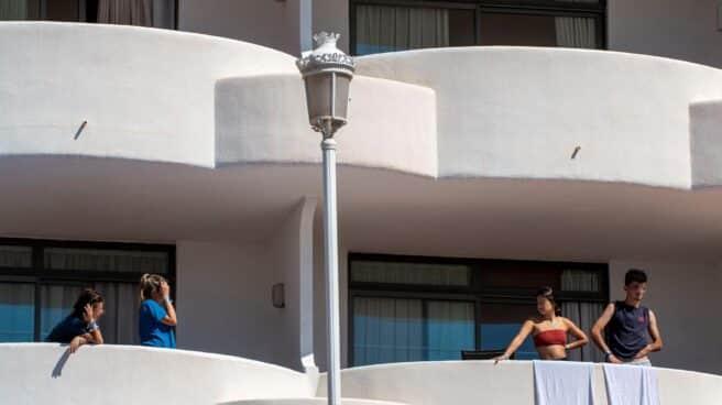 Varios estudiantes, asomados a las terrazas del hotel de Mallorca en el que permanecen aislados.