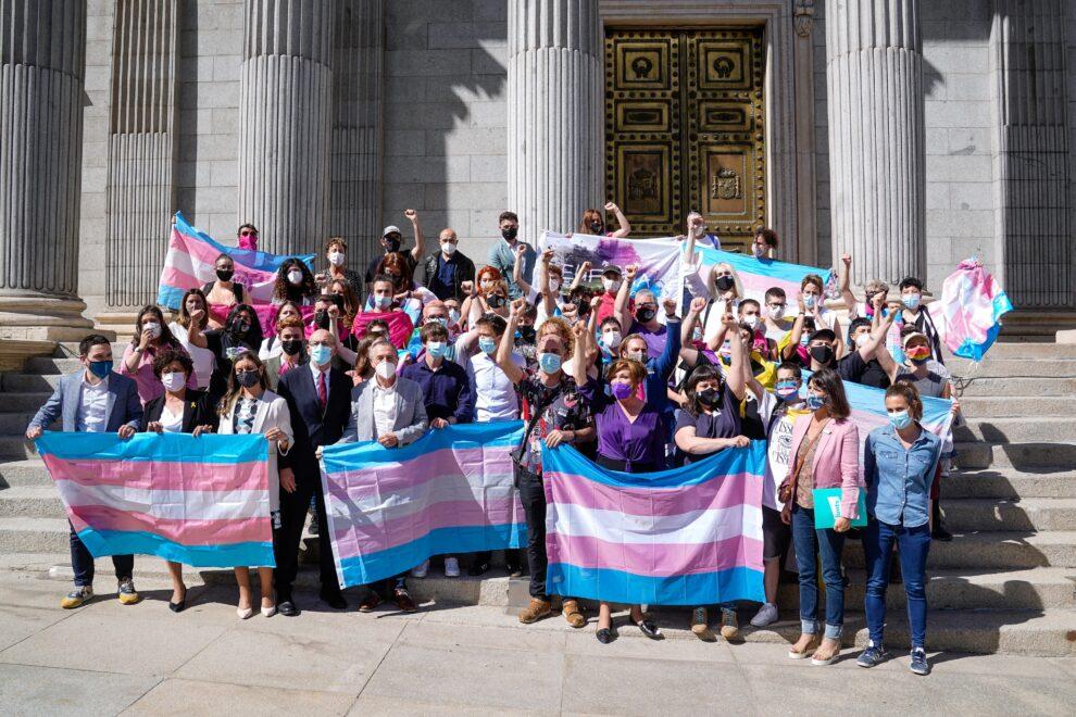 Varias personas y demás autoridades posan con banderas trans en las escaleras del Congreso