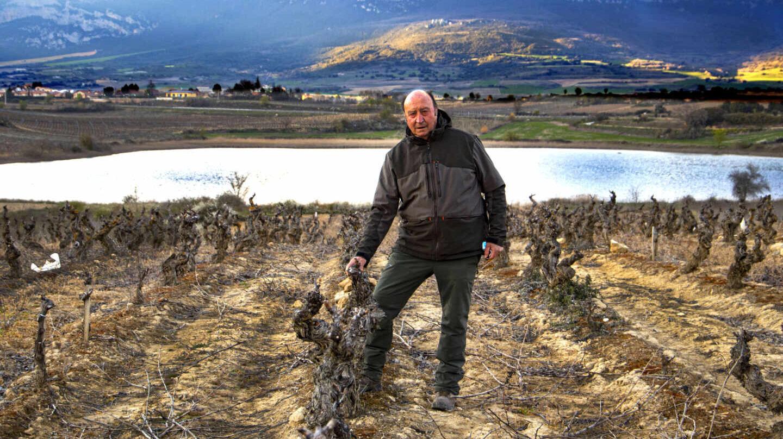 Florentino Martinez Monje, posa con el complejo lagunar con Laguardia (Álava) al fondo, rodeado de viñedos.