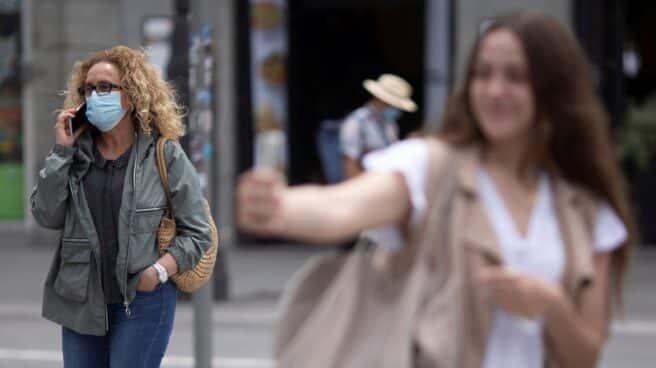 Una chica se hace un selfie en la Puerta del Sol de Madrid ante una mujer con mascarilla.