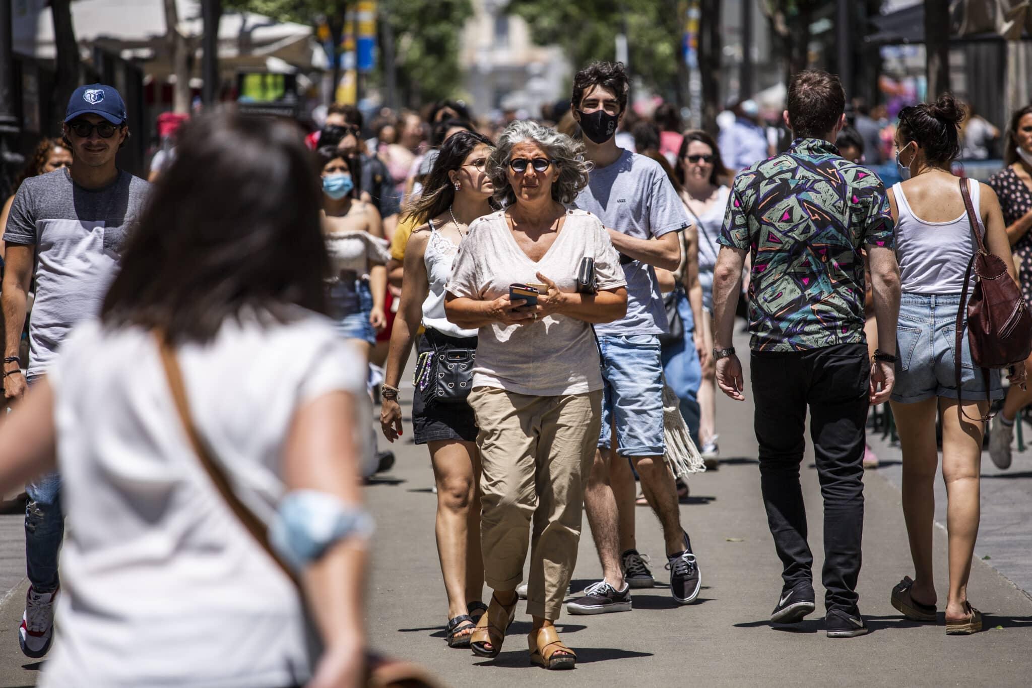 Una mujer pasea sin mascarilla por el centro de Madrid, durante el primer día en el que no es obligado el uso de la mascarilla en exteriores.