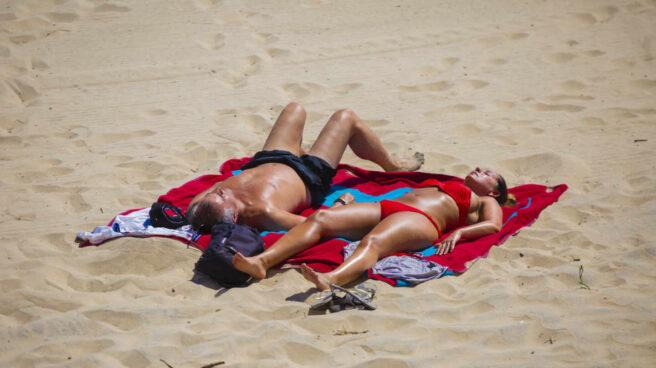 Una pareja toma el sol en la playa de Matalascañas.