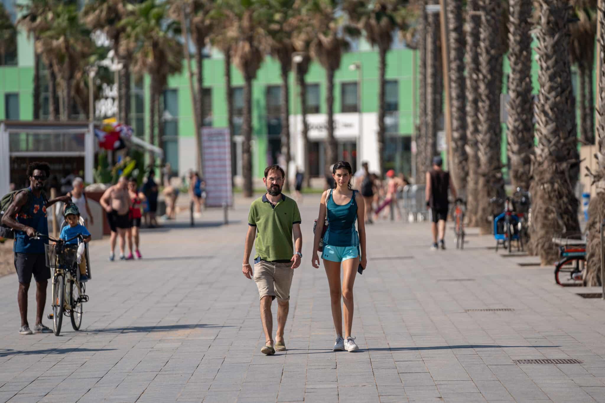 Una pareja pasea sin mascarilla delante del Hotel Vela, durante el primer día en el que no es obligado el uso de la mascarilla en exteriores.