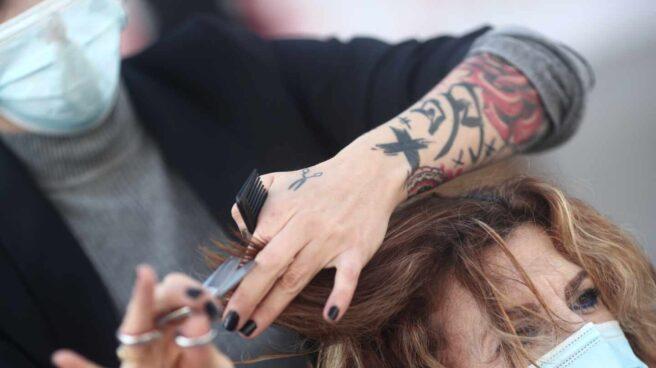 Una peluquera corta el pelo a una mujer .