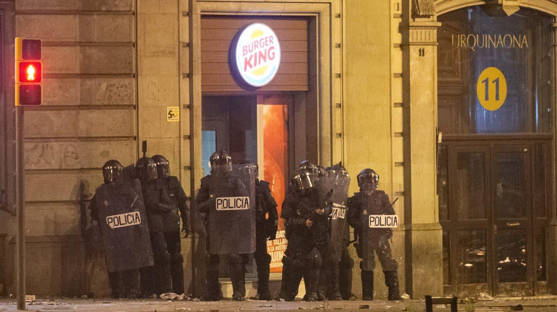 Agentes de la Policía Nacional, a las puertas de un establecimiento comercial durante los disturbios registrados en la barcelonesa Plaza de Urquinaona el 18 de octubre de 2019.