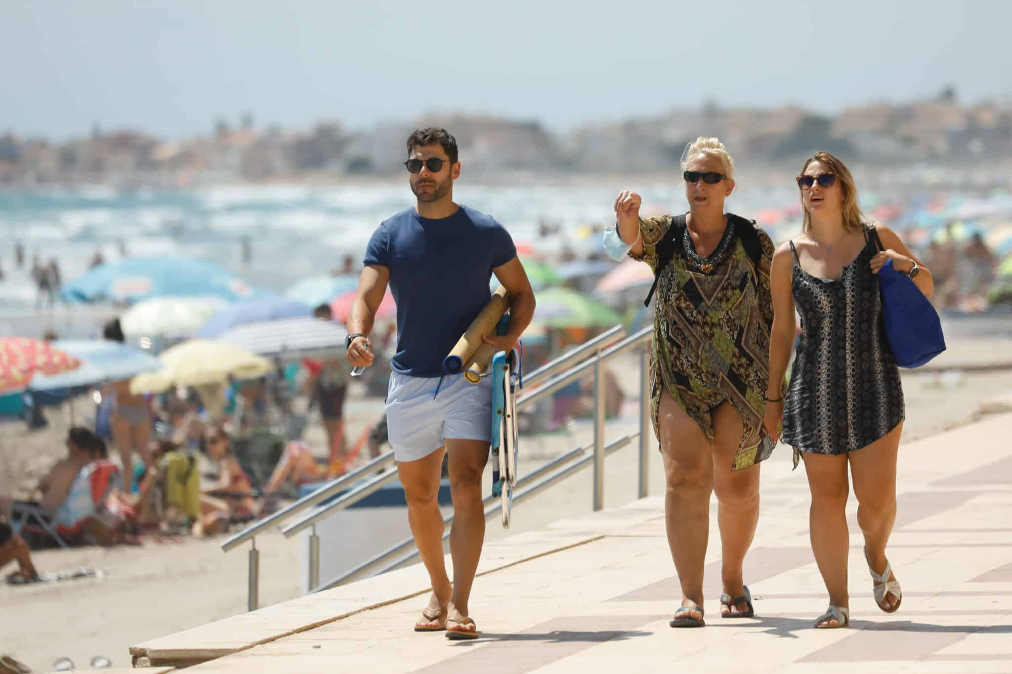 Tres personas caminan sin mascarilla, en el paseo marítimo de la playa de La Manga.