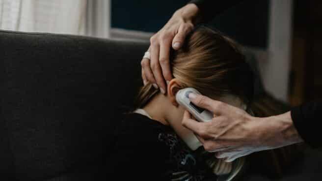 Un adulto pone un termómetro en el oído a una niña.