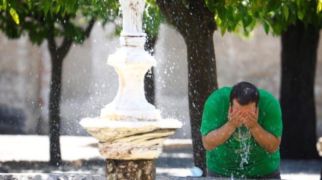 Un hombre se refresca en Córdoba.