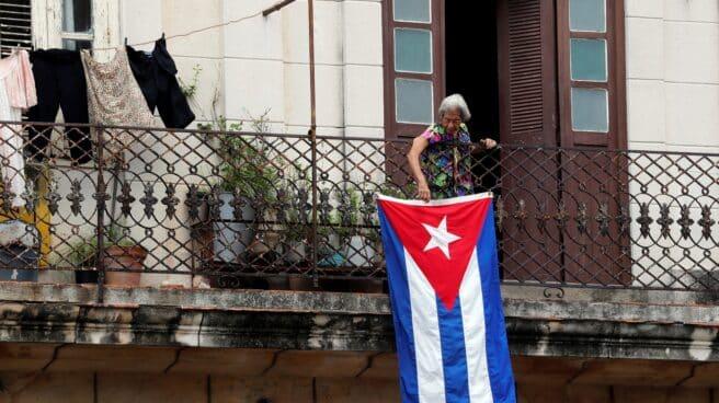 Una mujer en un balcón coloca la bandera cubana en La Habana