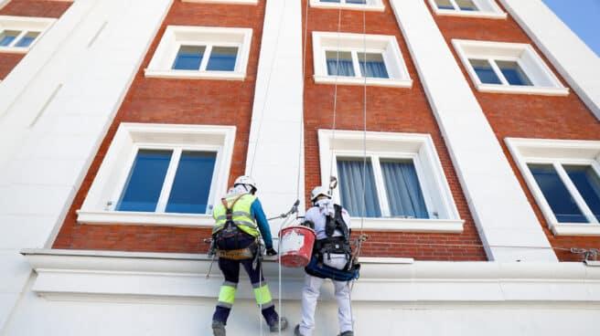 Dos operarios de obras, pintan parte de la fachada del edificio España.