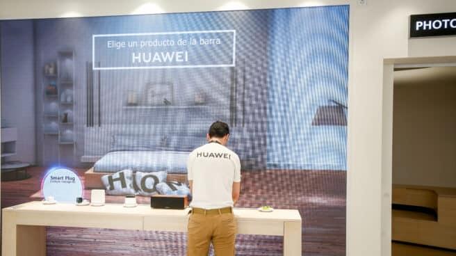Un empleado del Espacio Huawei de Madrid, ordena algunos de los productos de los expositores, el día de su apertura.