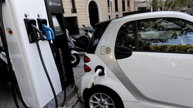 Un coche híbrido se carga en un punto de recarga de batería en Madrid.