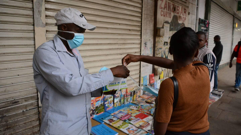 Una mujer compra una mascarilla en una calle de Nairobi, Kenia.