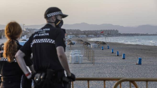 Dos policías locales contemplan la playa de la Malvarrosa