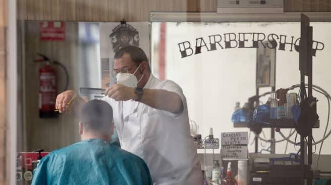 Un peluquero atiende a un cliente en el municipio gallego de Guitiriz, en Lugo, Galicia.