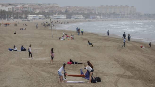 Varias personas en la playa la Malvarrosa en Valencia.
