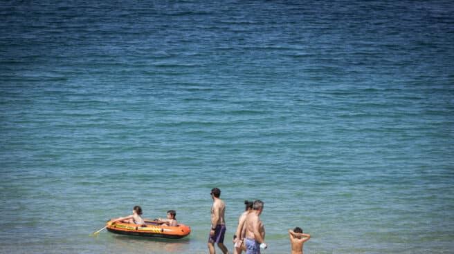 Varias personas se bañan y toman el sol en una playa del municipio de Marín, Pontevedra.