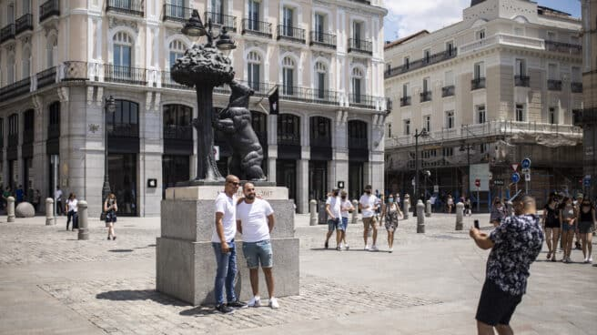 Un hombre toma una foto a otros dos, sin mascarilla en la Puerta del Sol.