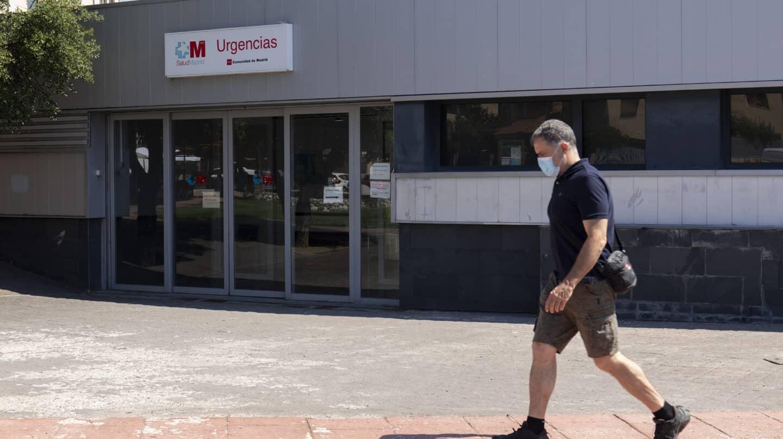 Un hombre pasea con mascarilla frente a unas Urgencias en Moralzarzal (Madrid).