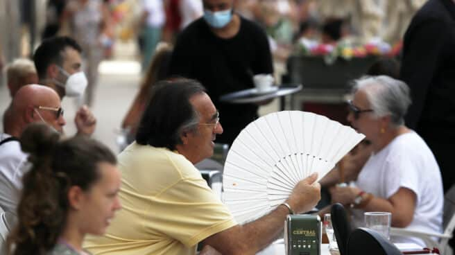 Un hombre se abanica en una terraza de Sevilla.
