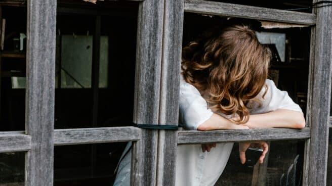 una joven con el móvil en la mano mira hacia el suelo apoyada en una ventana.