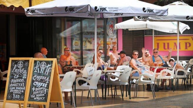 Varios turistas saludan al fotógrafo sentados en una terraza de Benidorm.