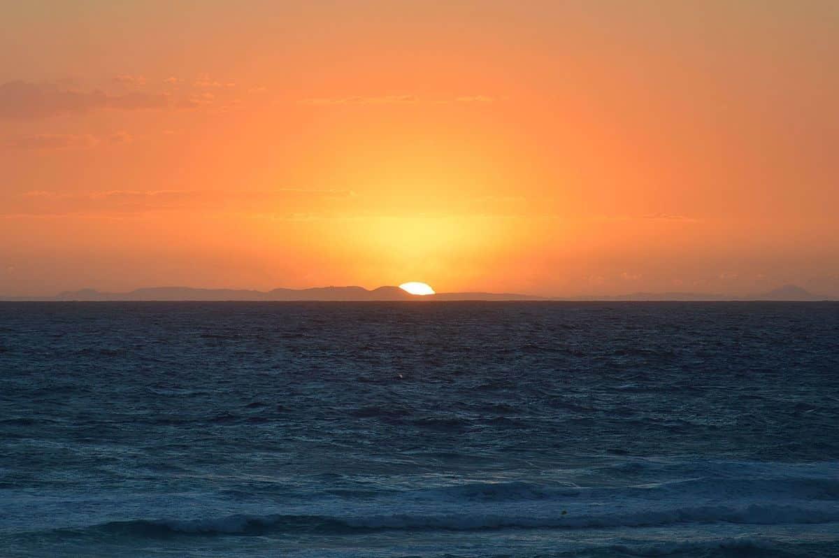 El sol se pone tras la isla de Mallorca, visto desde Menorca.