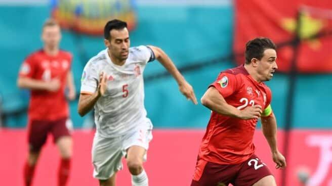Busquets defiende a un jugador suiza, con una bandera de Vietnam en el fondo, durante los cuartos de final de la Eurocopa.