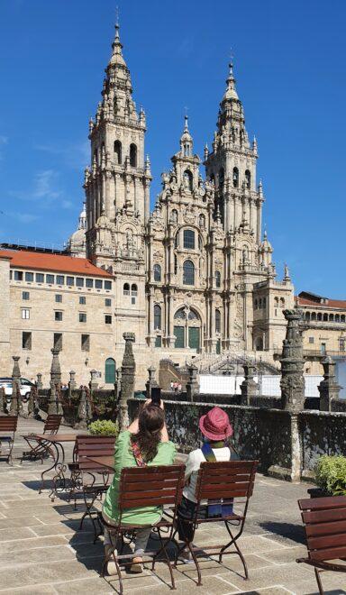 Dos turistas toman algo en una terraza en la plaza del Obradoiro