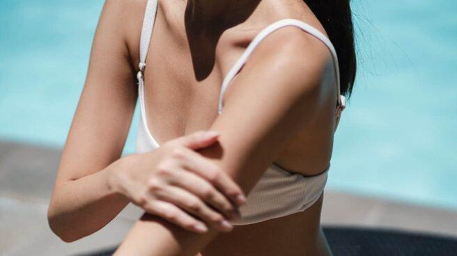 Mujer en bikini echándose crema de protección solar en el brazo