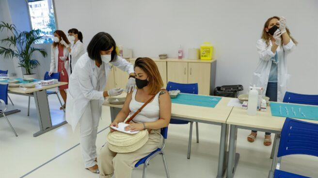 Fotografía de una mujer joven siendo vacunada en un centro sanitario por una enfermera