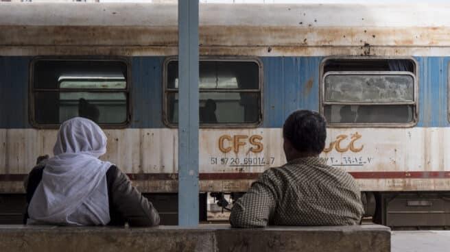 Dos hombres en la estación de Alepo frente a un tren abandonado