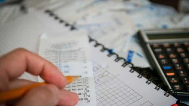 Una mano toma notas con unas facturas y una calculadora.