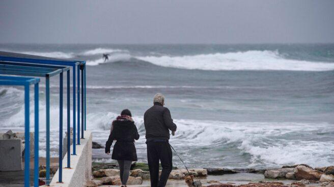 Dos personas caminan a la orilla de la costa de Biniancolla, en la isla de Menorca, en una imagen de archivo.