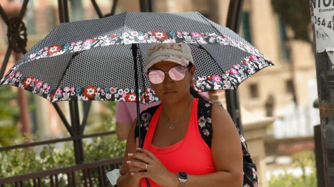Una mujer se protege del sol con un paraguas.