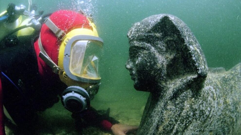 Un miembro del equipo, con una estatua hallada en Thonis-Heraclion