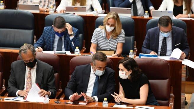 La presidenta de la Comunidad de Madrid, Isabel Diaz Ayuso (d) conversa con el consejero de Presidencia y Justicia de la Comunidad de Madrid, Enrique López , durante el pleno en la Asamblea de Madrid